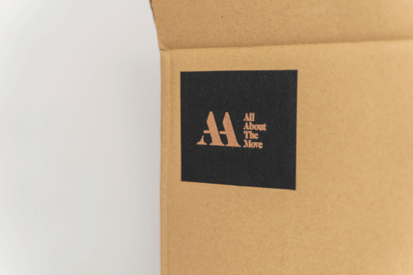 Brown packing box with All About The Move branding on it