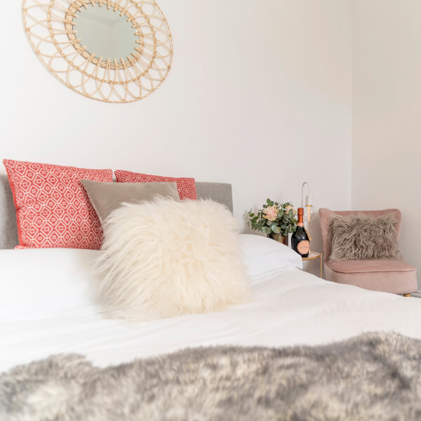 white bedding with pink and grey cushions