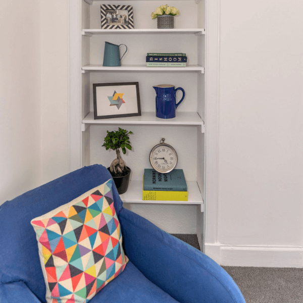 blue sofa chair with shelving behind